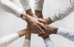 Hände von mehreren Personen, die übereinander liegen